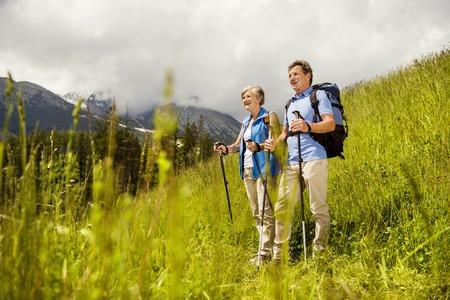 ancianos caminando: Pareja Senior turística de excursión en las montañas hermosas