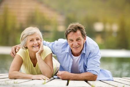 Senior couple lying down and having fun on pier photo