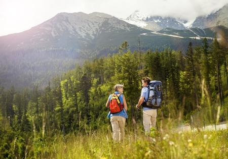 woman hiking: Senior tourist couple hiking at the beautiful mountains