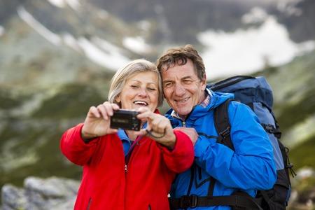 Senior tourist couple hiking and taking selfie at the beautiful mountains photo