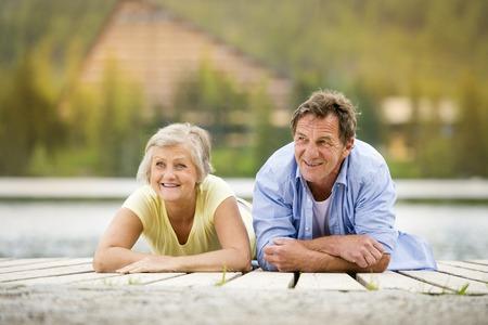 active couple: Senior couple lying down and having fun on pier Stock Photo