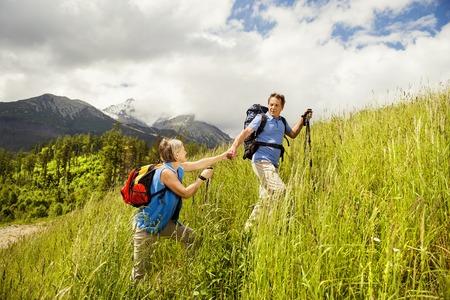 Senior tourist couple hiking at the beautiful mountains photo