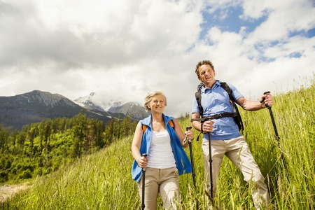 Senior tourist couple hiking at the beautiful mountains