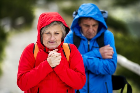 chilly: Senior tourist couple hiking at the beautiful mountains in cold weather
