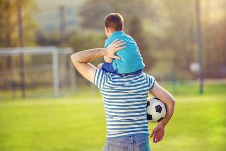 Joven padre con su pequeño hijo que se divierten en campo de fútbol Foto de archivo