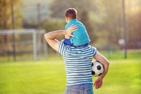 male parent: Young father with his little son having fun on football pitch Stock Photo