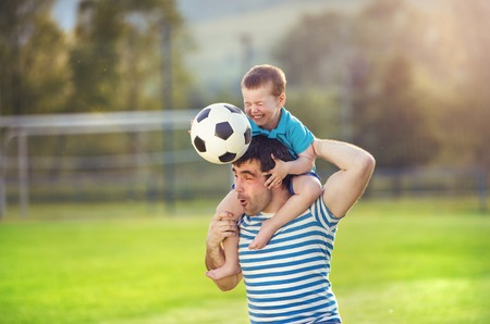 Young father with his little son having fun on football pitch Reklamní fotografie