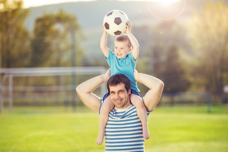 Young father with his little son having fun on football pitch Stock Photo
