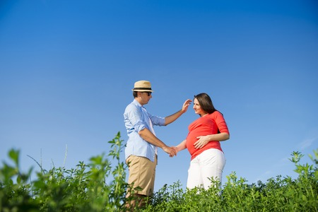 Portrait of young pregnant couple with blue sky photo