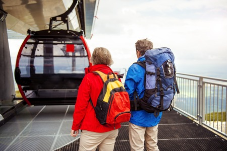 Senior hikers couple is waiting for cableway in cable station photo