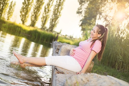 Outdoor portrait of beautiful pregnant woman holding her belly and relaxing by the lake photo
