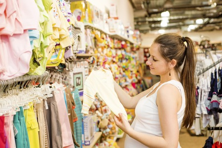 Young pregnant woman choosing baby clothes at baby shop store photo