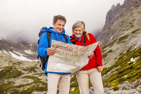 Senior hikers couple looking at the hike map during the hike in beautiful mountains photo