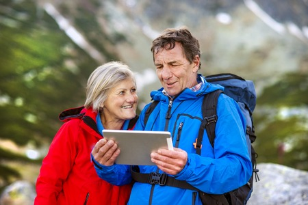 Senior hiking couple using travel app or map on tablet during the hike  photo