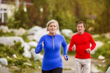 Senior paar joggen rond de Tarn in prachtige bergen, heuvels en hotel Stockfoto