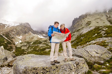 navigate: Senior hikers couple looking at the hike map during the hike in beautiful mountains
