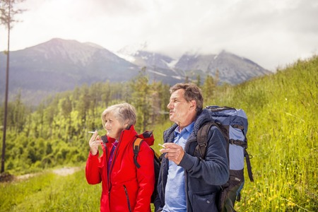 Senior hikers couple smoking during the walk in the mountains photo
