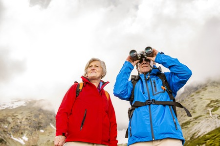 Senior hikers couple enjoying the landscape view with binoculars photo