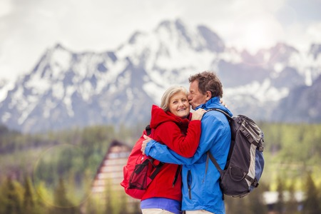 Senior hikers couple kissing during the walk in beautiful mountains, hills and hotel in background photo