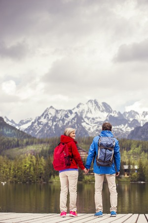Senior hikers couple during the walk round the tarn in beautiful mountains, hills and hotel  photo