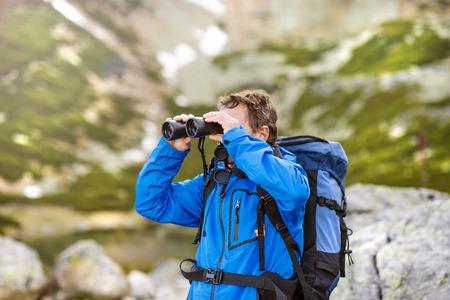 Älterer Wanderer Mann während der Wanderung genießen die schöne Landschaft Blick mit dem Fernglas Standard-Bild