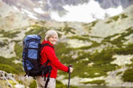 mature woman: Senior tourist woman hiking at the beautiful mountains
