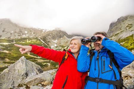 Senior hikers couple enjoying the landscape view with binoculars photo