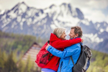 happy mature couple: Senior hikers couple hugging during the walk in beautiful mountains, hills and hotel