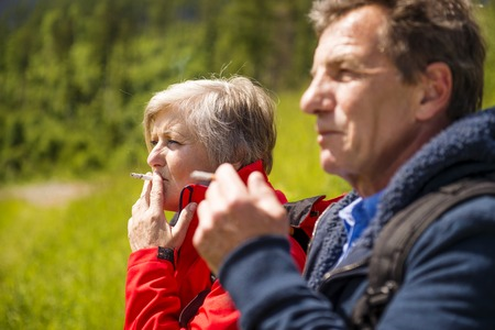 Senior hikers couple smoking during the walk in the mountains Stock Photo