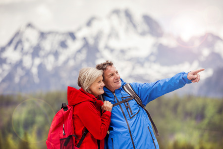 Senior hikers couple during the walk in beautiful mountains, hills and hotel