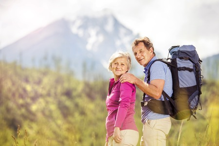 Senior tourist couple hiking at the beautiful mountains photo
