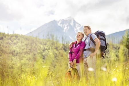 trekking: Senior tourist couple hiking at the beautiful mountains