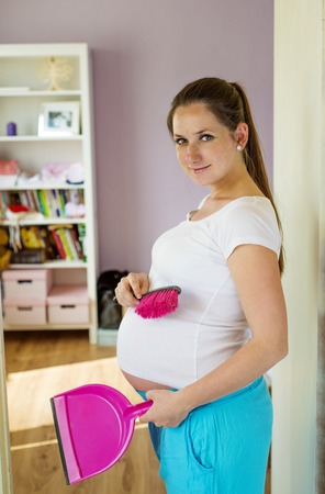 Portrait of beautiful pregnant woman holding dustpan and broom, cleaning home photo