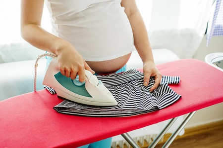 doing laundry: Portrait of unrecognizable pregnant woman ironing her future baby s clothes