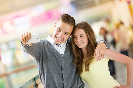 Young couple taking selfie with a cellphone in a shopping mall photo