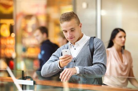 beau jeune homme: Beau jeune homme dans un centre commercial en utilisant t�l�phone mobile Banque d'images