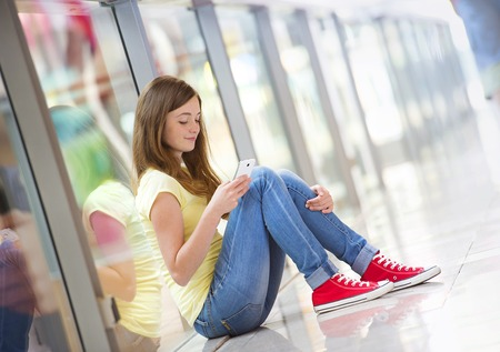 Pretty young girl sitting in a shopping mall and using her smartphone photo