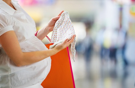 Young pregnant woman looking at new baby clothes in shopping mall photo