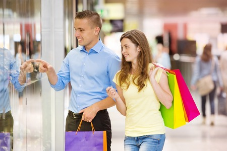 Happy young couple with bags in shopping mall photo