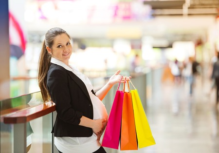 Young pregnant woman with shopping bags in shopping mall photo