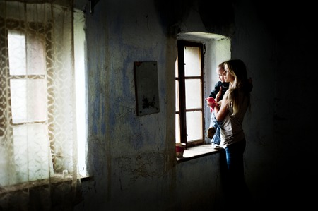 dark: Happy young mother with her son in old house Stock Photo