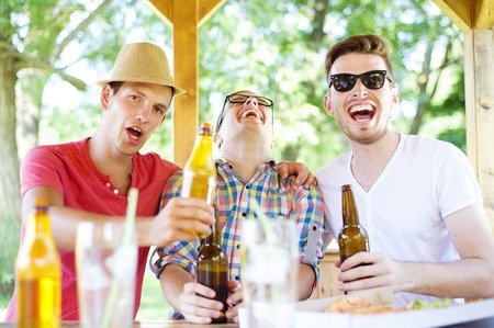 non alcoholic beer: Three happy friends drinking beer, chatting and having fun in pub garden