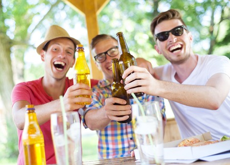 drunk party: Three happy friends drinking beer, chatting and having fun in pub garden