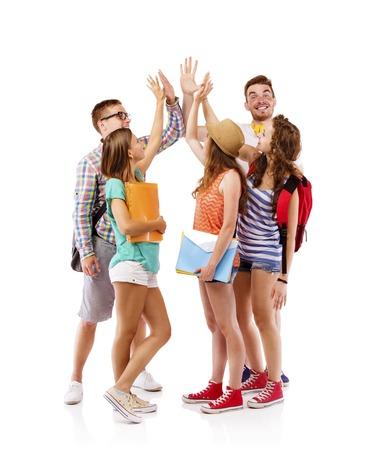 Groep gelukkige jonge tiener studenten staan en lachend met boeken en zakken geïsoleerd op witte achtergrond Stockfoto