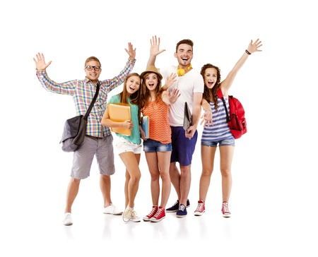 Group of happy young teenager students standing and smiling with books and bags isolated on white background