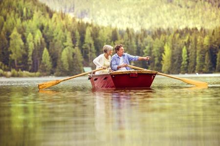 Anziano, coppia, paddling in barca con le montagne sullo sfondo
