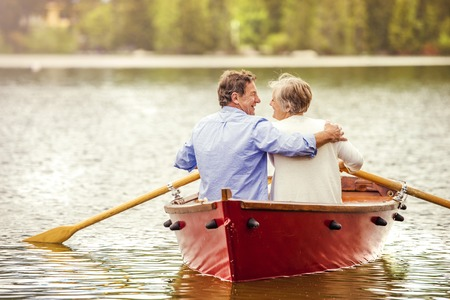 Senior couple paddling on boat on mountain tarn photo