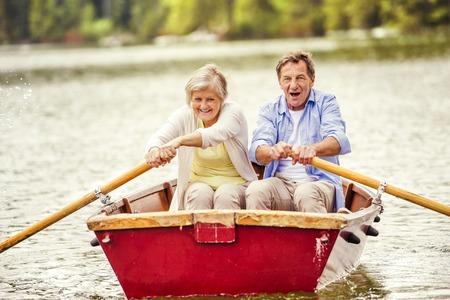 genießen: Ältere Paare, Paddeln auf dem Boot auf Bergsee