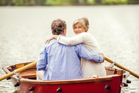 safe water: Senior couple paddling on boat on mountain tarn