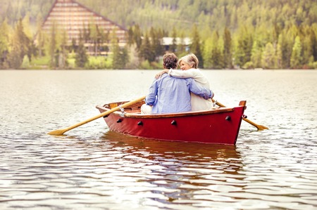 Senior couple paddling on boat with mountains in background photo
